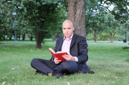 man with book sitting near a tree photo