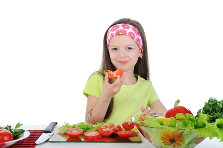 little girl cut fresh tomatoes. photo