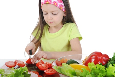Little girl cut salad at the table photo