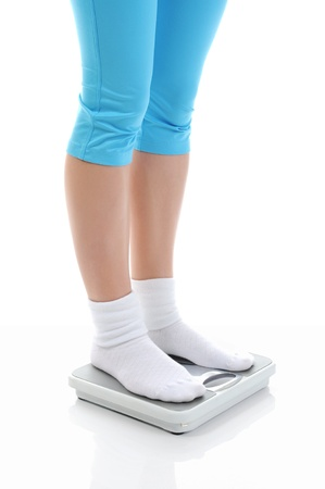 young athletic girl standing on the scales photo