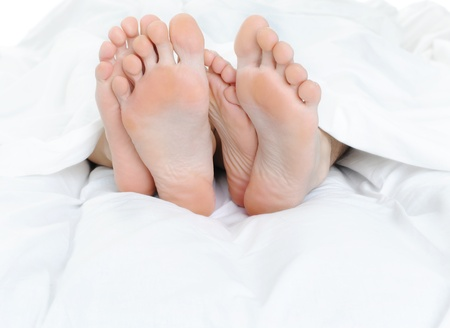 Close-up of the feet of a couple on the bed Stock Photo - 8954973