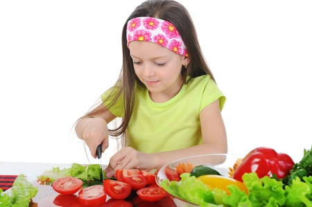 Little girl cut tomatoes at the table photo
