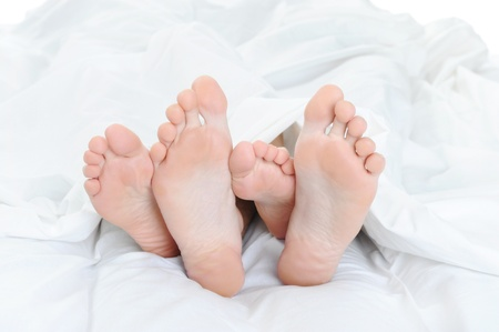 Close-up of the feet of a couple on the bed photo