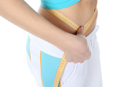 Young athletic woman measuring waist. photo