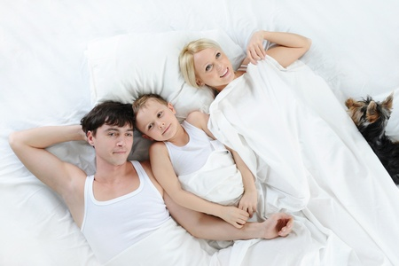 Happy family lying in bed photo