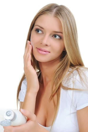 beautiful woman applying cream on her cheek photo