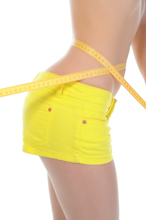 Young sports woman measuring waist. photo