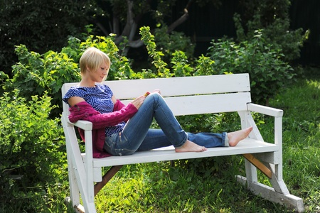 woman reading book in park photo
