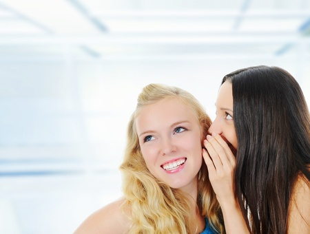 tattle: Two beautiful women telling secret