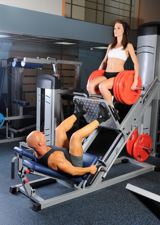 squats: man and a woman trained in the gym