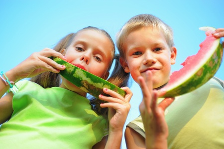 Young girl and boy eating watermelon photo