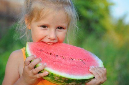 Young girl eating watermelon photo