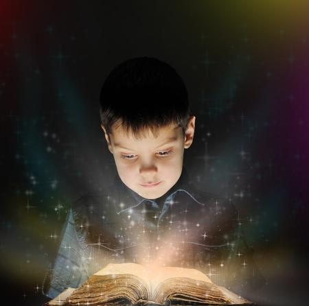 lezing: Jongen leest een magisch boek Stockfoto