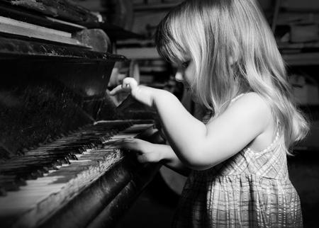 piano: ni�a jugando en un piano Foto de archivo