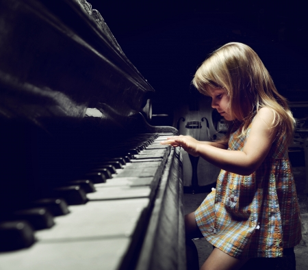girl playing on an  piano  photo