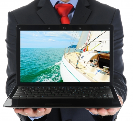navigating: Businessman holding an open laptop
