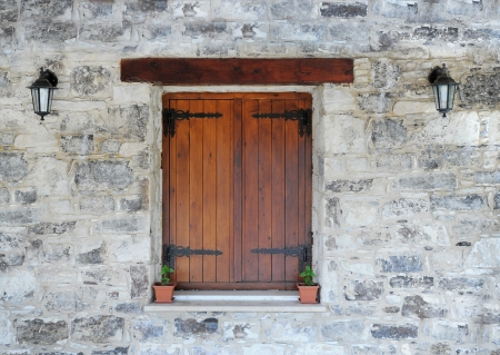 Wooden window in the stone wall photo