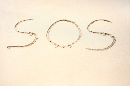 Drawing of  SOS  on the beach sand photo