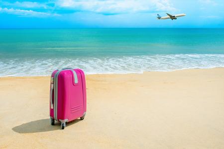 arrive: Suitcase at the sunny beach near the sea