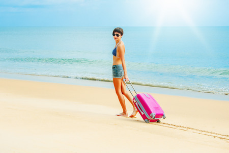 arrive: Young woman with a suitcase on the beach Stock Photo
