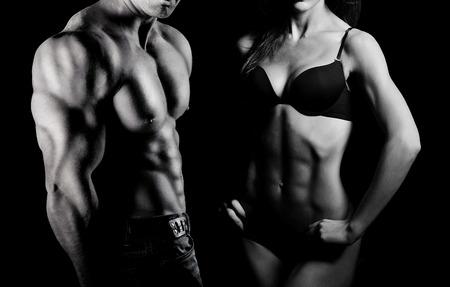 보디 빌딩. 강한 남자와 검은 배경에 포즈 여자