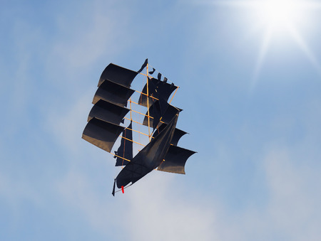 Black ship flying in the sunny sky photo