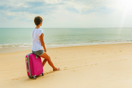 Young woman with a suitcase on the beach photo