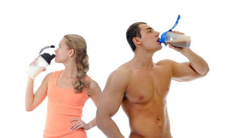 Athletic young man and woman with protein shake bottle. Isolated on white background photo
