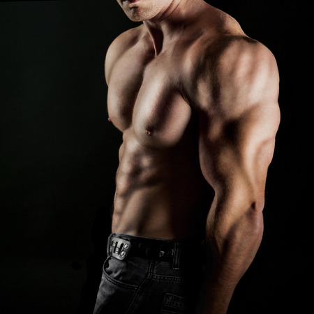 Bodybuilder showing his muscles. on a black background photo