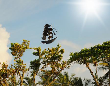 doomed: Black ship flying in the sunny sky Stock Photo