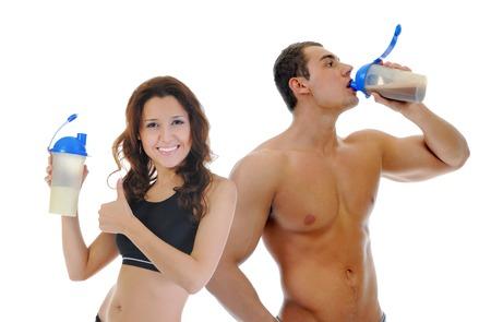 salud y deporte: Hombre joven atl�tico y de la mujer con una botella de batido de prote�nas. Aislado en el fondo blanco