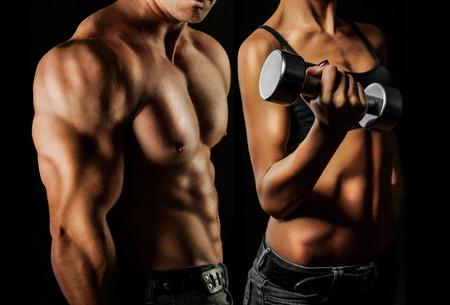 белки: Бодибилдинг Сильный мужчина и женщина, создавая на черном фоне Фото со стока
