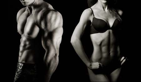 Bodybuilding  Strong man and a woman posing on a black background Фото со стока