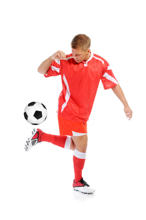 soccer boots: Image of a young football player with the ball in the red uniform  Isolated on white background Stock Photo
