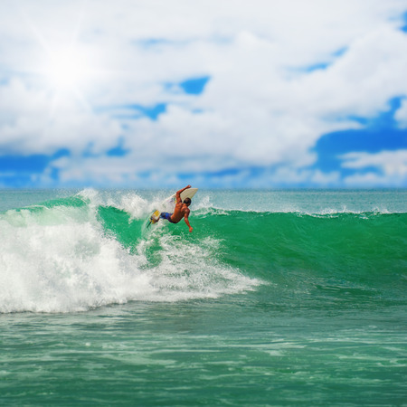 Athletic surfer with board on a wave in the ocean