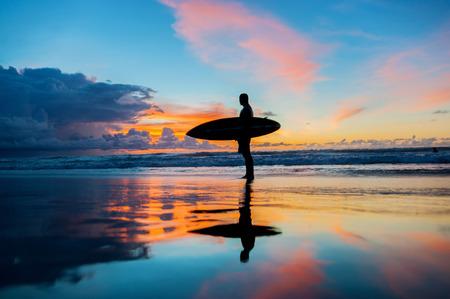 ビーチでボードを持つ若いサーファー 写真素材