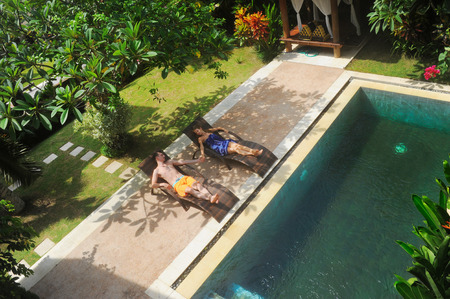 swimming pool home: young couple of people relax on villa by swimming pool