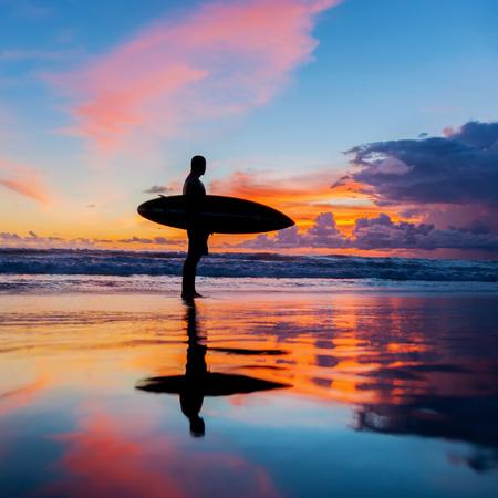 Jeune surfeur avec le Conseil sur la plage
