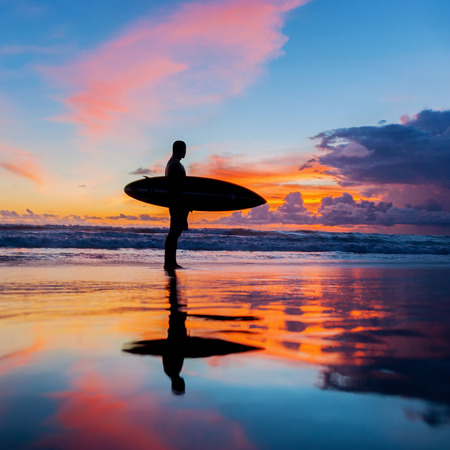 Young surfer with board on the beach Stock Photo