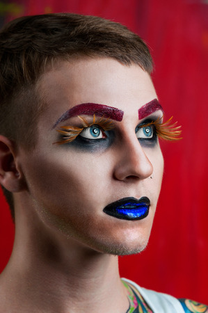 Close-up portrait of the handsome young man fashion model with make-up and big eyelashes photo