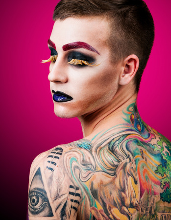 eye tattoo: Close-up portrait of the handsome young man fashion model with make-up and big eyelashes