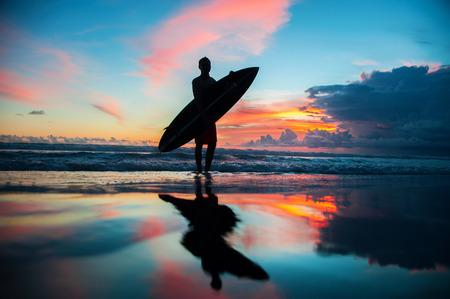 Jonge surfer met bord op het strand Stockfoto