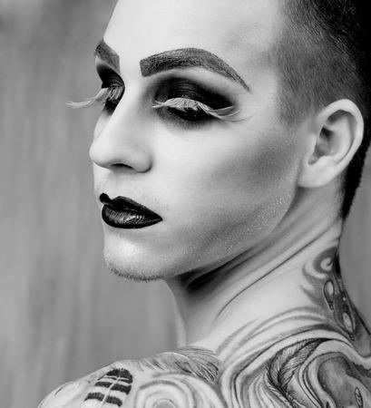 hombres gays: Close-up retrato de la modelo de moda joven y apuesto hombre con el maquillaje y las pestañas grandes
