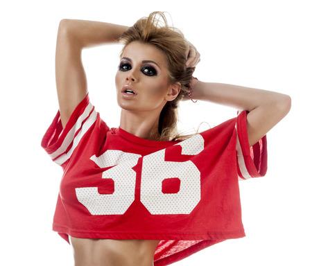 porrista: Animadora joven hermosa en un uniforme rojo con el pelo largo. Aislado en un fondo blanco Foto de archivo