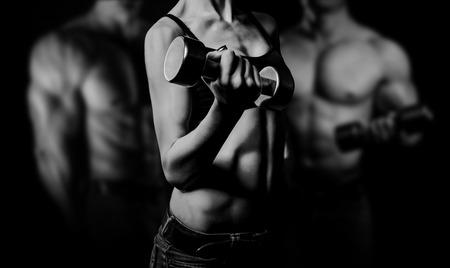 Bodybuilding. Sterke man en een vrouw die zich voordeed op een zwarte achtergrond