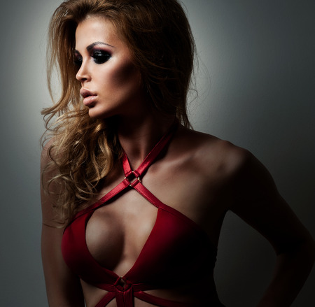 red lingerie: Fashionable young woman in red swimsuit with long curly hair. Bblonde posing in studio on black background Stock Photo