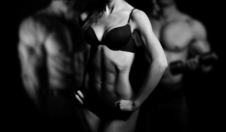 black man white woman: Bodybuilding. Strong man and a woman posing on a black background