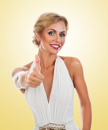 tumb: Smiling woman showing tumb sign. Isolated on white background Stock Photo