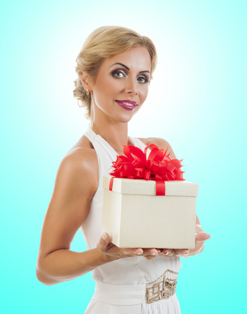Young happy woman with a gift on color background 版權商用圖片