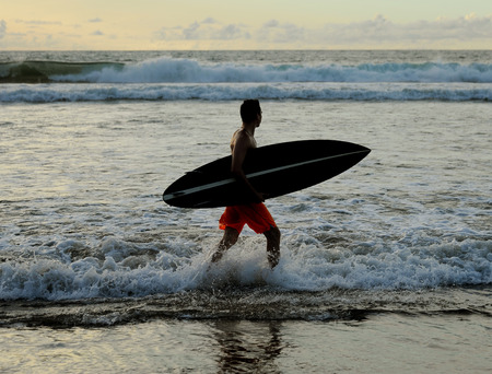 Young surfer with board on the beach 版權商用圖片
